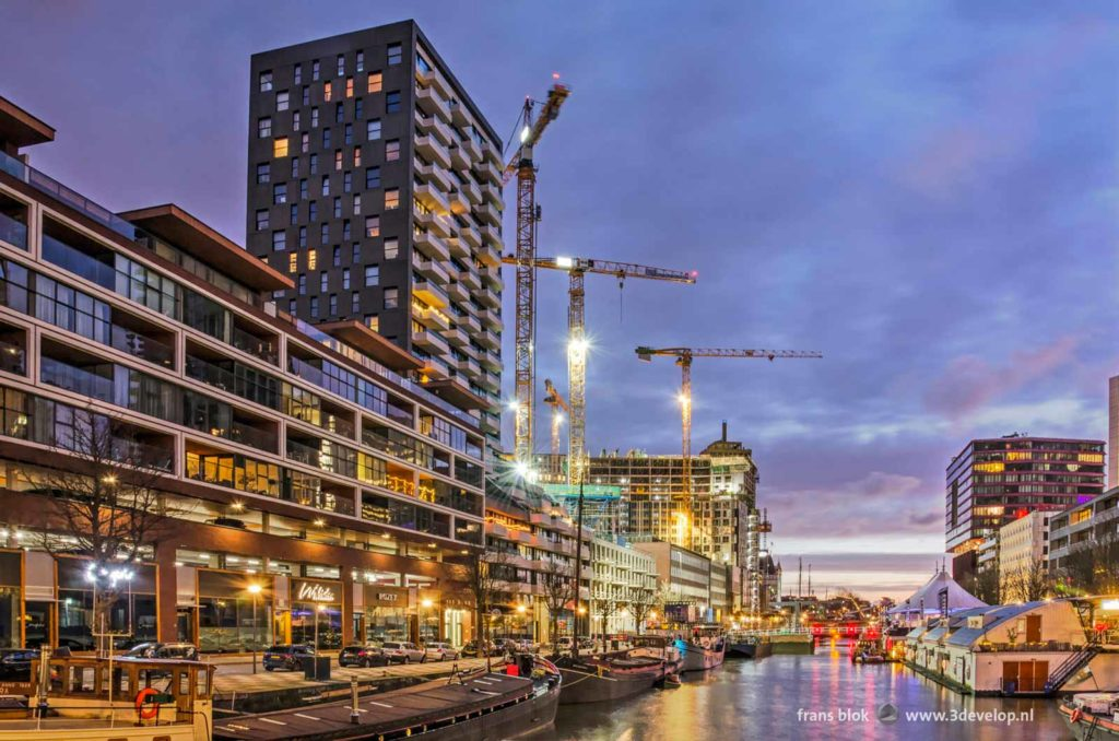 Wijnhaven harbour in Rotterdam, The Netherlands during the blue hour before sunrise with various residential buildings, some of them completed, others under construction