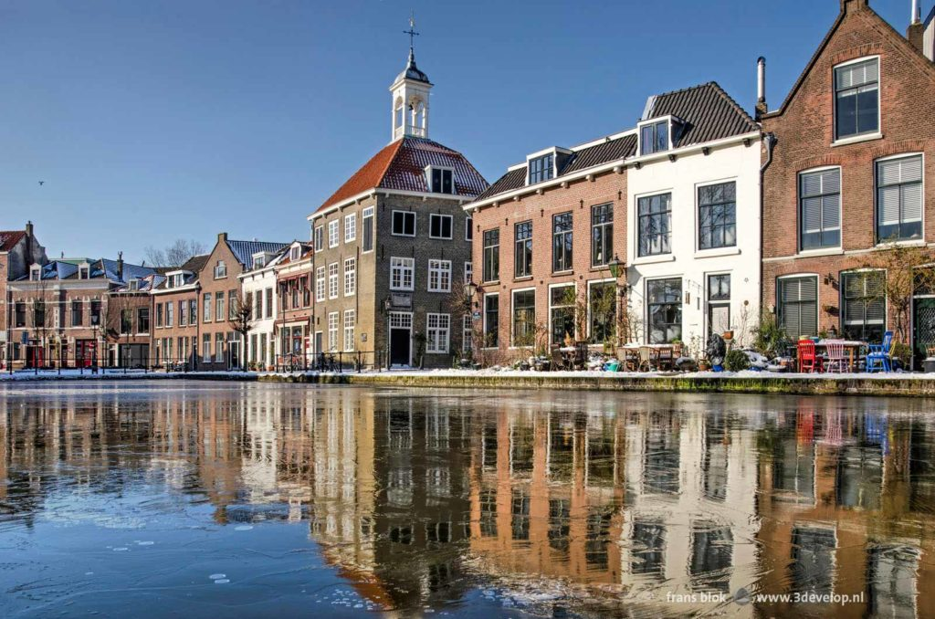The Bag Carriers house and other historic buildings reflect in the thin ice on Schie river in Schiedam, The Netherlands on a sunny day in the winter of 2021