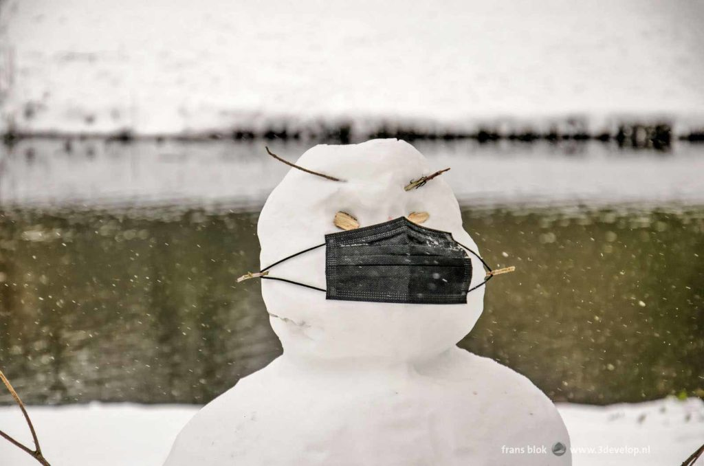 Snowman with a black facemask in The Park in Rotterdam during the winter of 2021