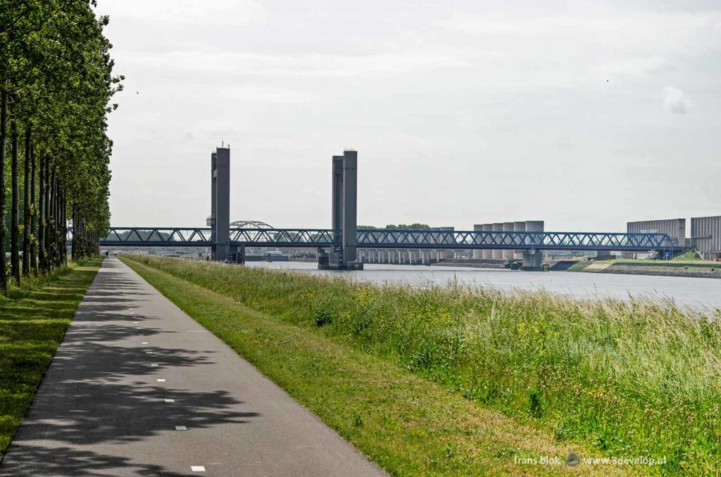 Path for bicyclists and pedestrians along Caland canal in the Europoort area near Rotterdam-Rozenburg with in the background Caland bridge and the concrete windscreen
